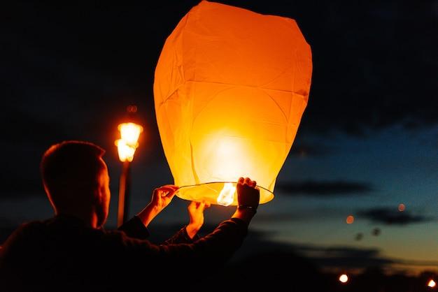 's avonds, bij zonsondergang, lanceren mensen met hun familieleden en vrienden traditionele lantaarns