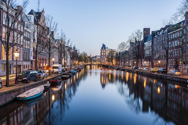 's avonds in amsterdam, nachtcityscape met gebouwen en rivier