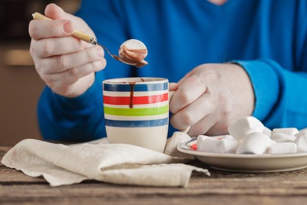 's avonds ontspannen, mok gevuld met warme chocolademelk en marshmallow en snoep