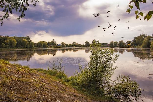 's avonds wolken boven de rivier. bomen worden weergegeven in het heldere water van het meer