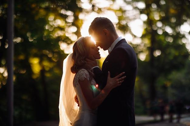 's avonds zomerzon maakt een halo rond mooie bruidspaar