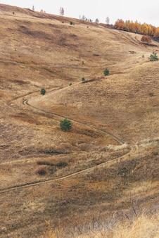 S bocht van onverharde weg op de heuvel