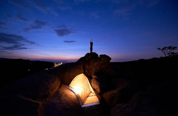 's nachts kamperen op rotsformatie. toeristentent en vrouw die yoga op bergbovenkant doen
