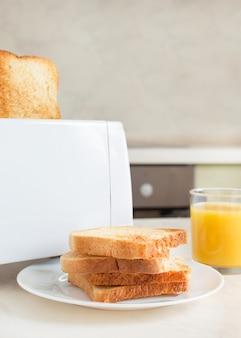 's ochtends een europees ontbijt in de keuken. witte elektrische broodrooster met jus d'orange met toast.