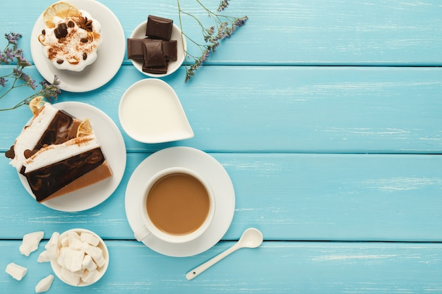's ochtends koffie achtergrond. border cappuccino-kop, melkpot, chocolade, kleine cakes en geraffineerde suiker op blauwe rustieke houten tafel, kopieerruimte, bovenaanzicht