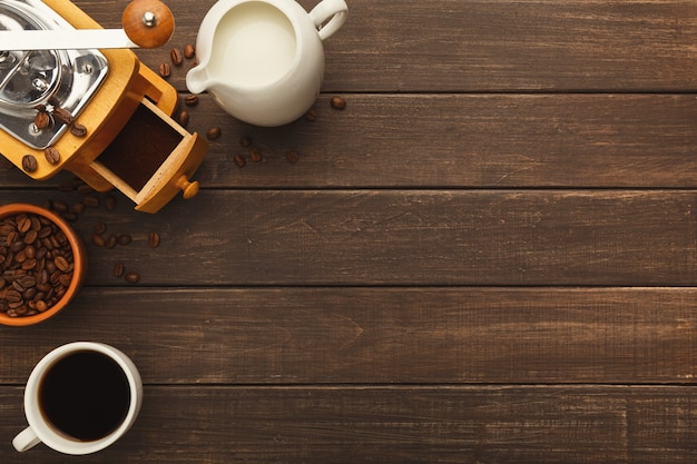 's ochtends koffie achtergrond. rand van kopje bittere americano, hele en gemalen bonen, melkpot en vintage grinder op rustieke houten tafel, kopieer ruimte, bovenaanzicht