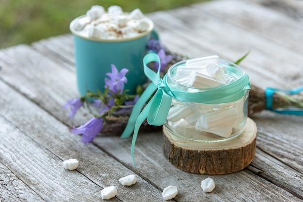 's ochtends koffie drinken met marshmallow plakjes op een houten achtergrond.