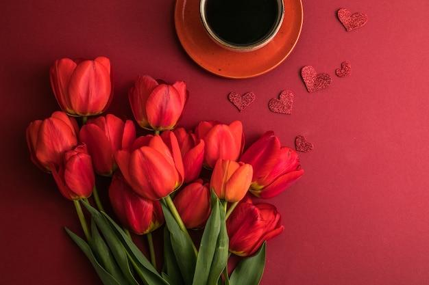 's ochtends koffie en een boeket rode tulpen op een felrode ondergrond