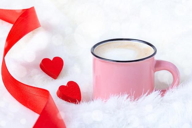 's ochtends koffie in bed met een paar rode harten en lint voor valentijnsdag