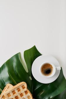 's ochtends koffie in beker met toast en plant blad