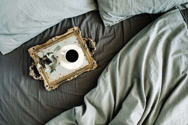 's ochtends koffie op gouden vintage dienblad in bed met grijs laken en kussens