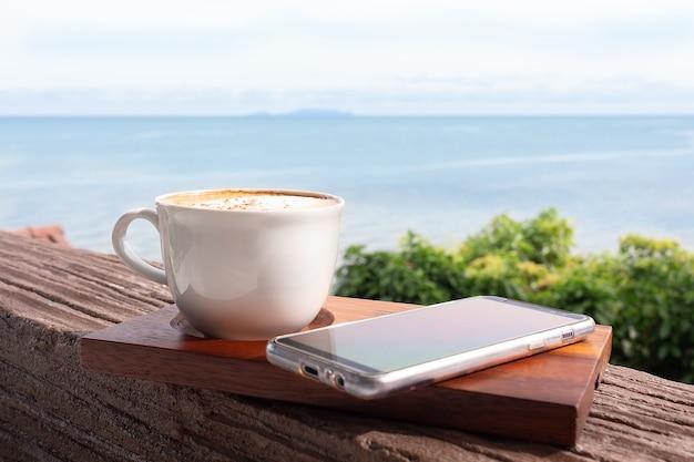 's ochtends koffie op houten dienblad met mobiele telefoon en zeegezicht.