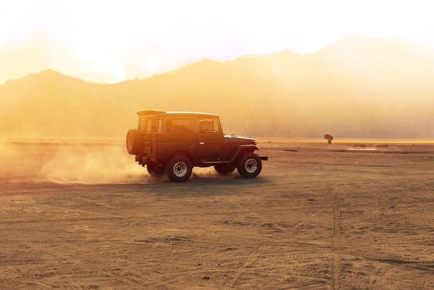 's ochtends rijdt er een auto over de offroad-woestijn. outdoor avontuurlijk leven