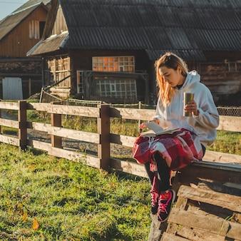 's ochtends zit het meisje op een houten bankje in de bergen in de natuur, leest een boek en drinkt hete thee uit een thermobeker. concepten lezen in de natuur. buitentraining