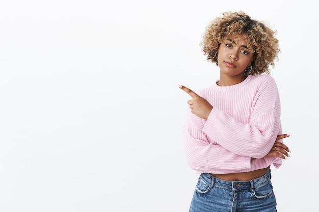 Saai, dus uit de mode. teleurgesteld somber en overstuur schattig afro-amerikaans cool meisje met doorboorde neus en blond afro-kapsel kantelend hoofd fronsend, mokkend ontevreden, wijzend naar de linkerbovenhoek