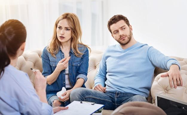 Saai gesprek. leuke verveelde jongeman die in het kantoor van de psycholoog zit en niet deelneemt aan de discussie terwijl hij zich verveelt