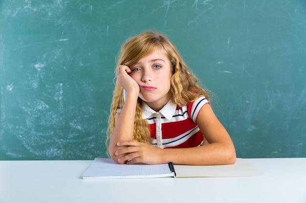 Saai triest uitdrukking student schoolmeisje op het bureau