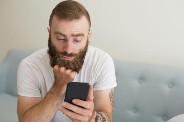 Saaie knappe bebaarde man met behulp van smartphone in de woonkamer