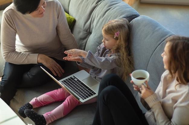 Saamhorigheid. gelukkig liefdevol gezin. oma, moeder en dochter brengen samen tijd door. film kijken, laptop gebruiken, lachen. moederdag, feest, weekend, vakantie en kindertijd concept.
