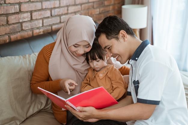Saamhorigheid van een klein meisje met haar ouders bij het lezen van een boek