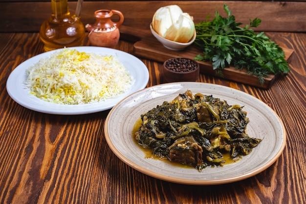 Sabzi pilaf rijstvlees met het zijaanzicht van spinaziekruiden