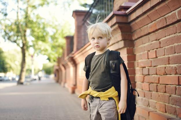Sad benadrukte kleine jongen met rugzak.