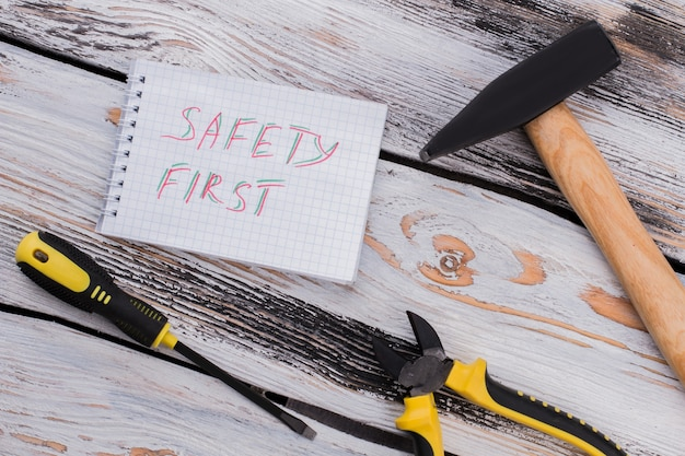 Safety first notice en huishoudelijke reparatietools. bovenaanzicht plat lag. oude houten achtergrond.