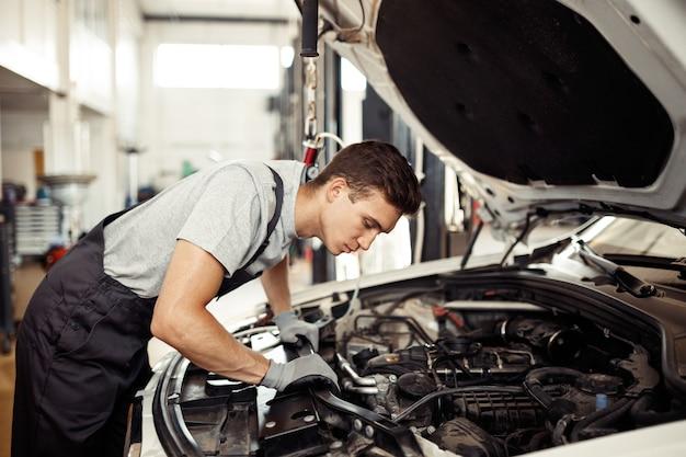 Safety sirst: een knappe automonteur controleert de motor.