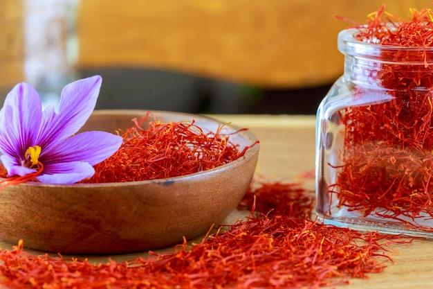 Saffraan stigma's verspreid op een houten oppervlak van een glazen fles. saffraan krokus bloemen. bloeiende saffraan sativus.