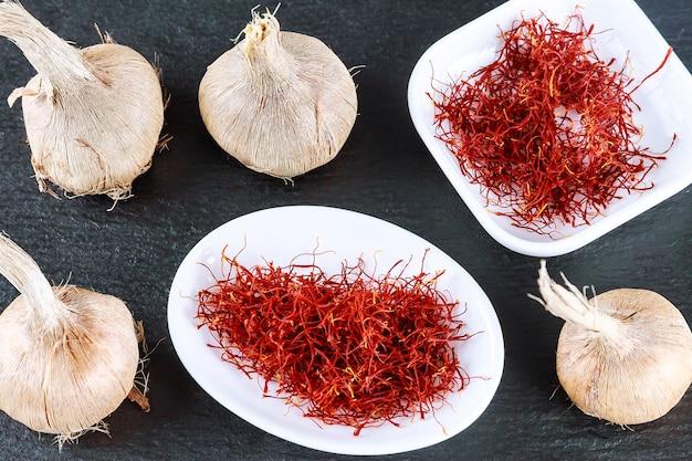 Saffron sativus bol en droog kruid van saffraan op een zwart bord op. rode meeldraad van saffraan in witte plaat.