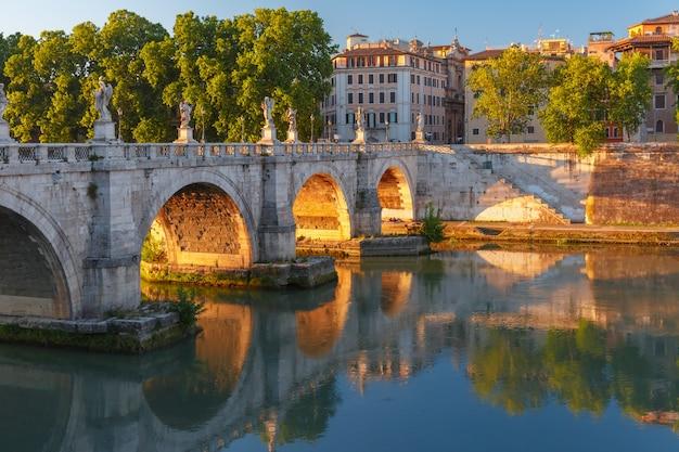 Saint angel-brug met spiegelreflectie in de rivier de tiber bij zonsondergang in rome, italië.