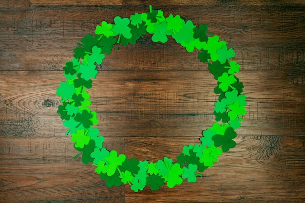 Saint patrick's day. cirkelvorm van groene drie bloembladklavers op houten achtergrond
