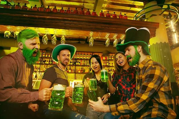Saint patrick's day-feest. gelukkige vrienden vieren en drinken groen bier. jonge mannen en vrouwen die groene hoeden dragen. pub interieur.