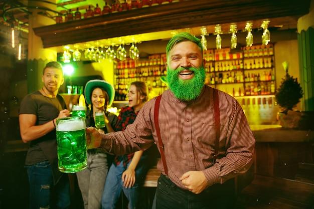 Saint patrick's day-feest. gelukkige vrienden vieren en drinken groen bier.