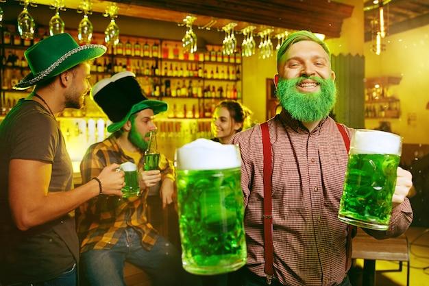 Saint patrick's day-feest. gelukkige vrienden viert en drinkt groen bier. jonge mannen en vrouwen die groene hoeden dragen. pub interieur.