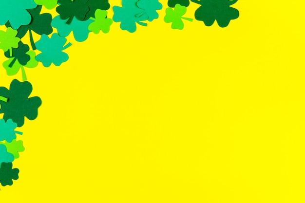 Saint patrick's day. groene drie bloemblaadjeklavers die op gele achtergrond liggen