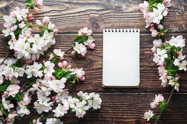Sakura-bloesems op donkere rustieke houten achtergrond met een notitieboekje. de lenteachtergrond met tot bloei komende abrikozentakken en kersentakken