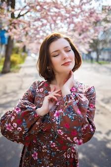 Sakura takken met bloemen aan een boom in de straten van de stad. gelukkig vrouw meisje spinnen op straat met bloeiende sakura. sakura bloeit.