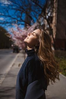 Sakura takken met bloemen aan een boom in de straten van de stad. stijlvolle vrouw meisje loopt op straat met bloeiende sakura. schitterend modieus meisje buitenshuis. sakuraboom bloeit.