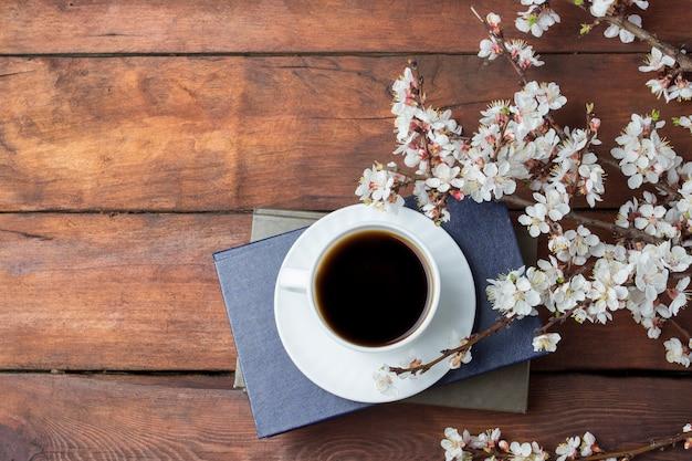 Sakura-takken met bloemen, witte kop met zwarte koffie en boek op een donker houten oppervlak. plat lag, bovenaanzicht