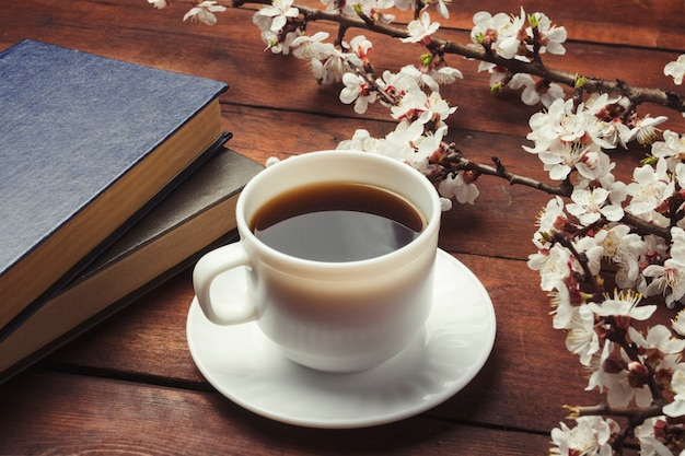Sakura-takken met bloemen, witte kop met zwarte koffie en twee boeken op een donkere houten ondergrond. concept van de lente