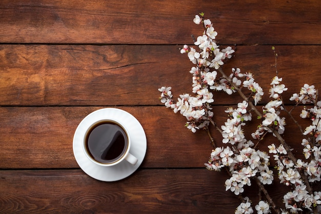Sakura-takken met bloemen, witte kop met zwarte koffie op een donkere houten ondergrond. plat lag, bovenaanzicht