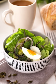 Salade bereid met verse groene bladeren, ui en gekookt kippenei
