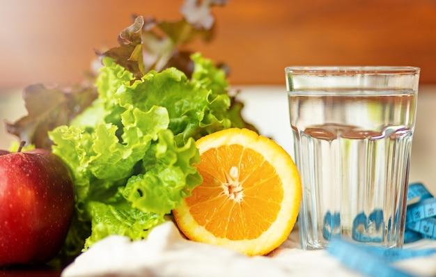 Salade blad. sinaasappel, kopje water en het meten van blauwe tape op bruine achtergrond, gezonde levensstijl en drinkwater concept