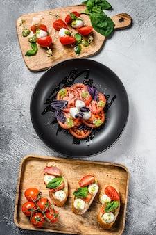 Salade caprese, spiesjes, canapeetjes, bruschettes met kerstomaatjes, mozzarella en basilicum. grijze achtergrond. bovenaanzicht