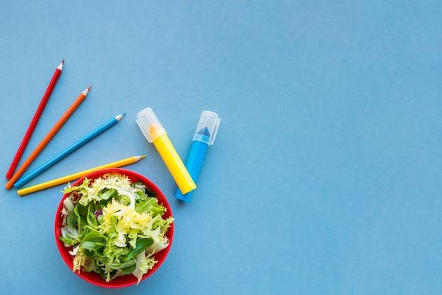 Salade dichtbij potloden en tellers