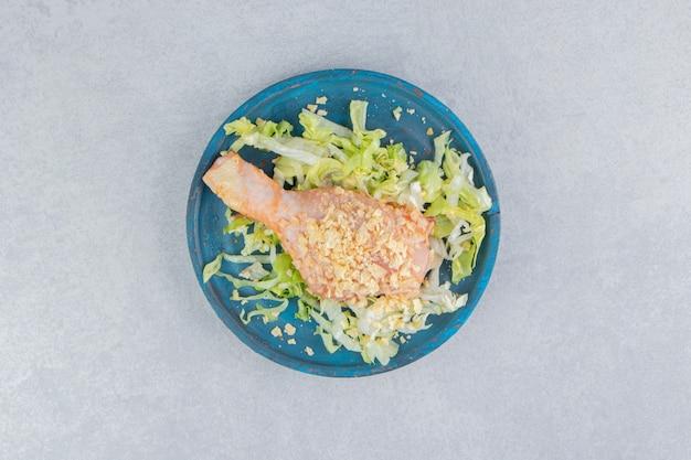 Salade en kippenpoot in de houten plaat, op het blauwe oppervlak