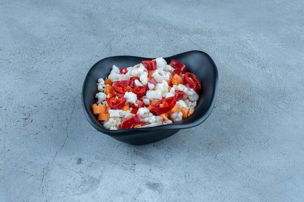 Salade gemaakt van bloemkool, peper en wortelen in een zwarte kom op marmer.