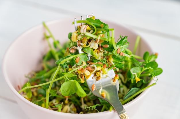Salade gemaakt van erwten microgroene spruiten en gekiemde bonen in een kom op grijs