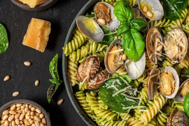 Salade gemaakt van pasta fusilli, zeevruchten vongole, spinazie, parmezaanse kaas en pijnboompitten in een bord op zwarte tafel